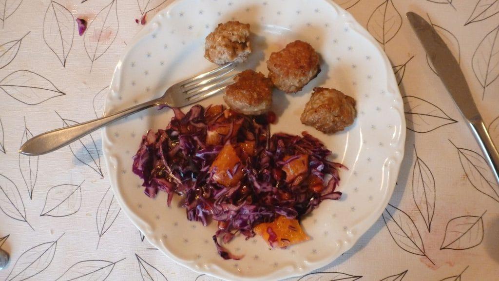 Kipgehaktballetjes op een wit bord met rode koolsalade