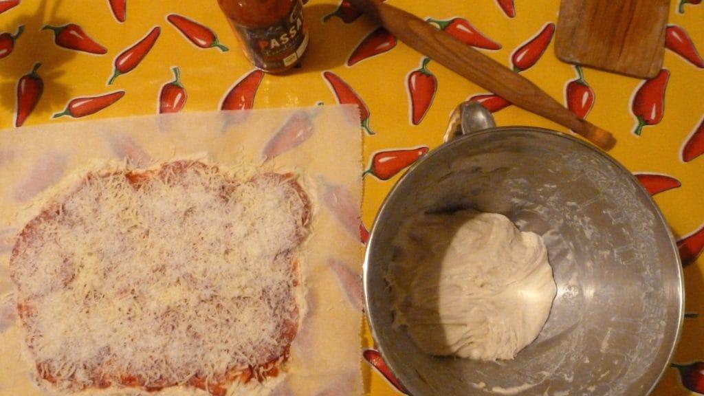 Pizzadeeg in kom naast belegd pizzadeeg