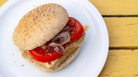 Wit bordje met een bruin broodje met sesamzaad waar dikke plakken tomaat met gebakken ui uit steken