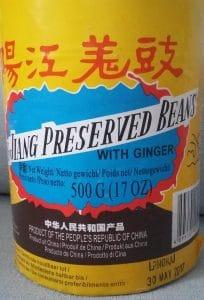 Foto van verpakking van preserved black beans, met een gele achtergrond, rode Chinese karakters en in het zwarte de woorden Jiang preserved beans