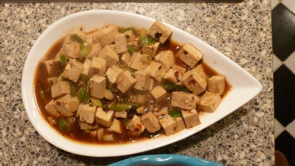 Blokjes tofu in rode saus met groene snippers bosui