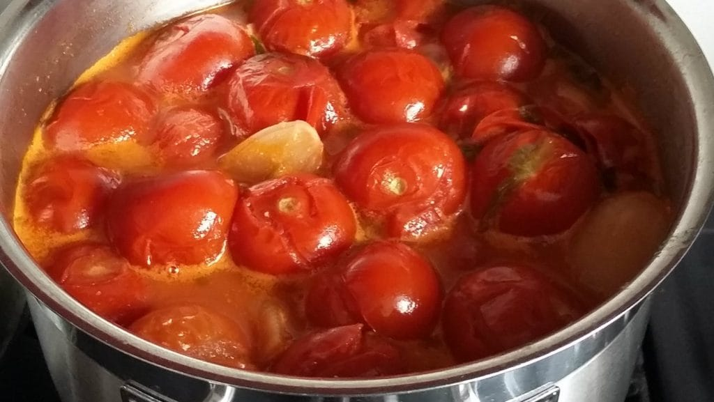 Tomaten met gebarsten velletjes in oranje soep