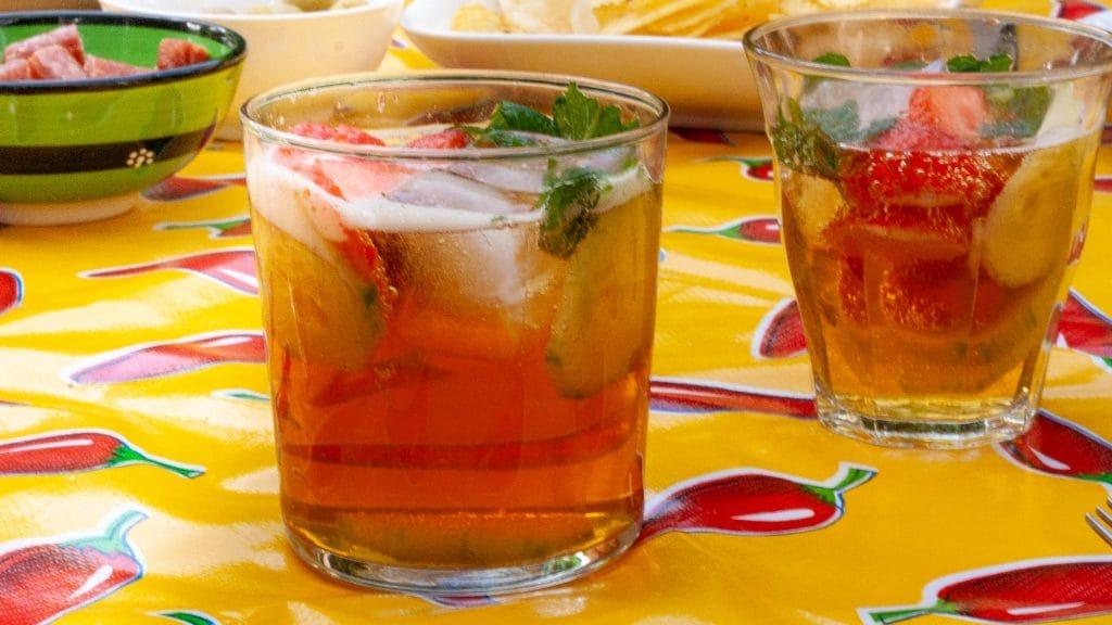 Glas Pimm's cup; bruin vocht met belletjes, groene blaadjes en schijfjes komkommer