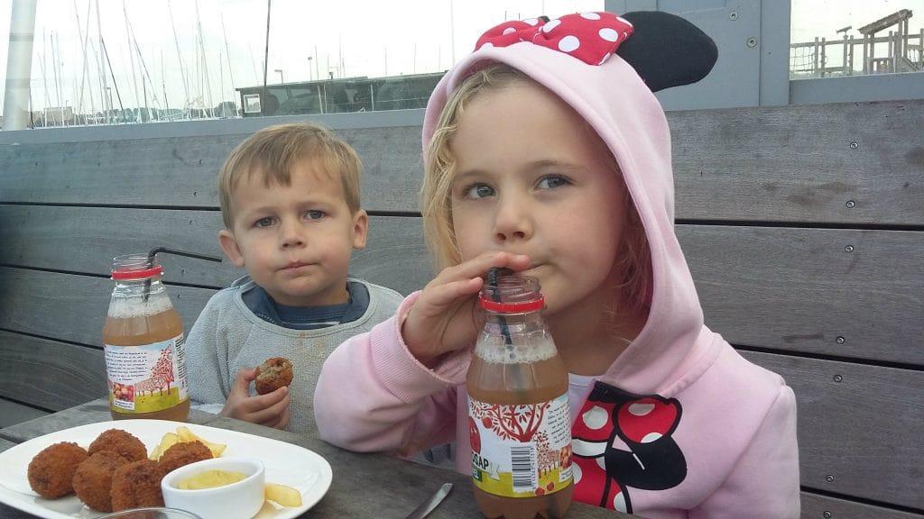 Meisje met flesje sap en jongetje met bitterbal