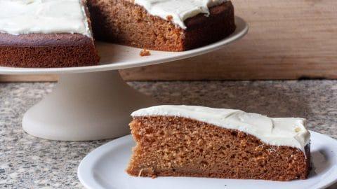 Punt lichtbruine cake met wit laagje icing met op de achtergrond de hele cake op een plateau