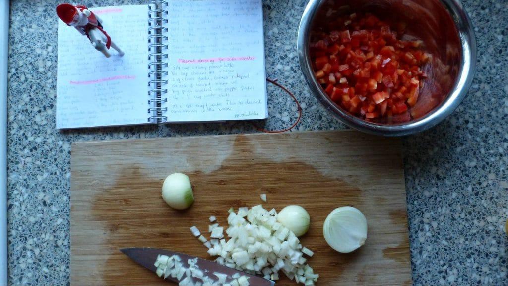 Snijplank met gesnipperde ui en bak met blokjes paprika