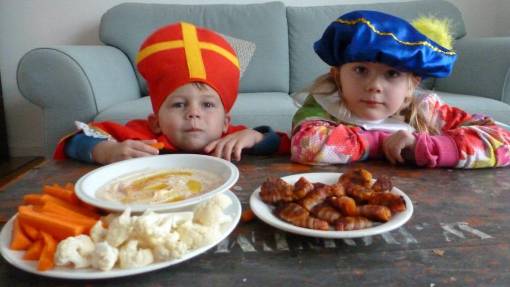 Schaal met groente en hummus en schaal met abrikozen in spek met kinderen op de achtergrond