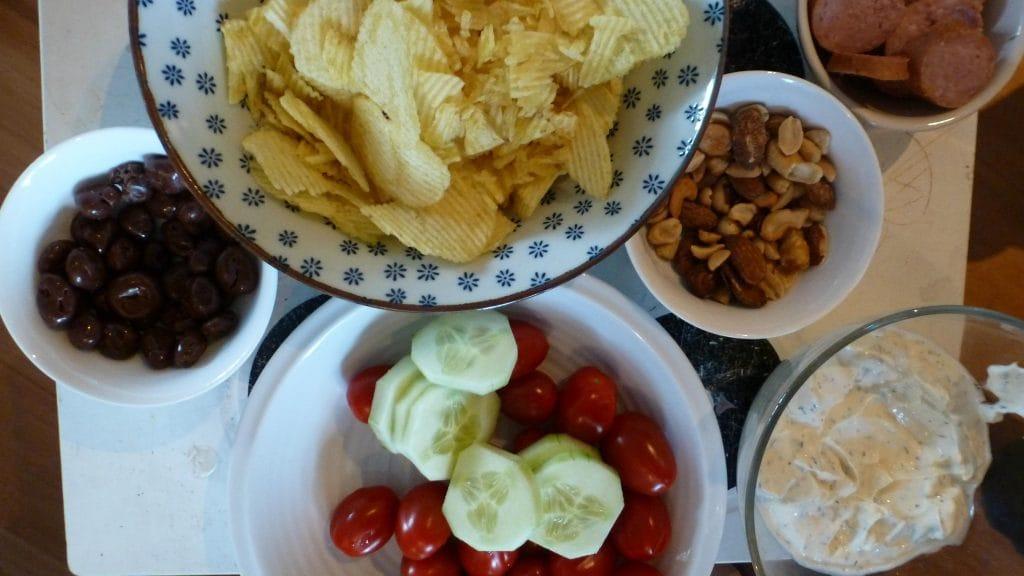 Foto van chips, tomaatjes, komkommer, dip, worst, nootjes en chocoladerozijnen
