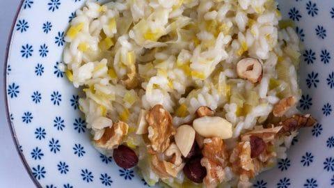 Kom met blauwe bloemetjes met daarin roomwitte risotto met zachtgroene sliertjes prei, bestrooid met gehakte noten