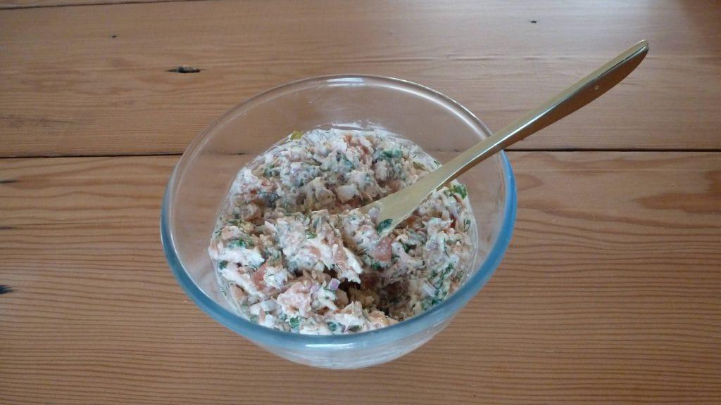 Glazen schaaltje met wit-roze zalm pureen en gouden vork