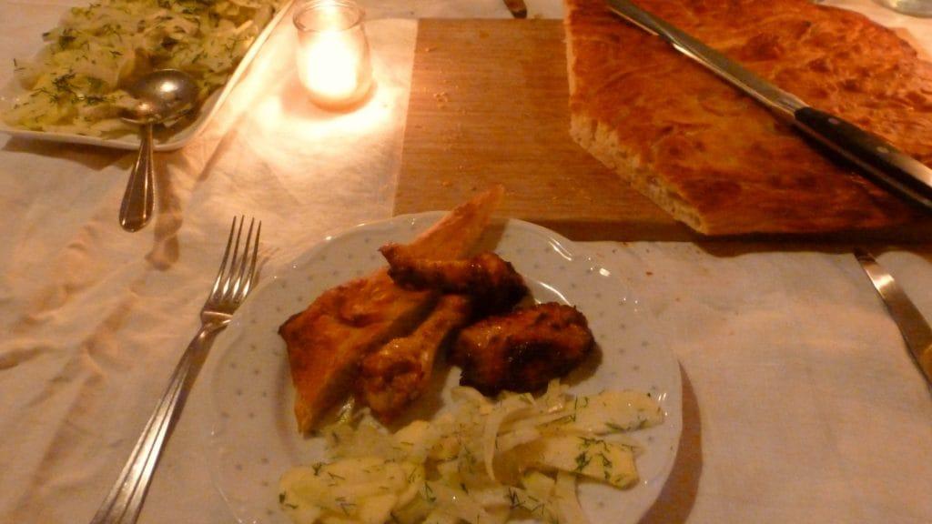 Bord met kip brood en salade met op de achtergrond schalen en een kaarsje