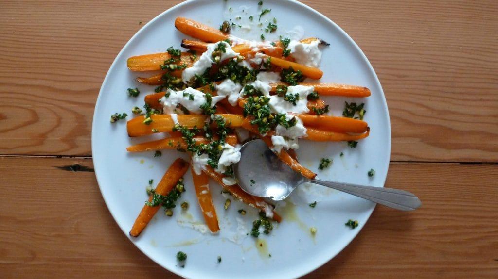 Bord met worteltjes, witte kaas en groene kruidensaus