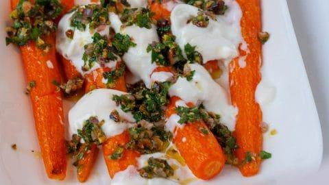 Witte schaal met worteltjes met witte klodders burrata en wat groene saus erover gesprenkeld