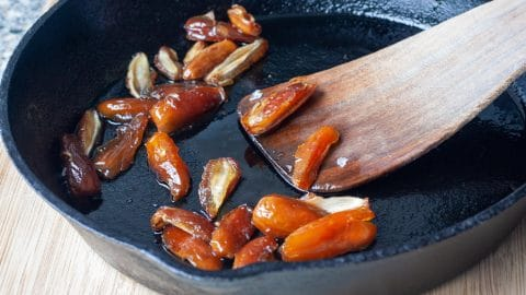 Oranje-bruine halve dadels in een zwarte koekenpan met aan de zijkant een spatel