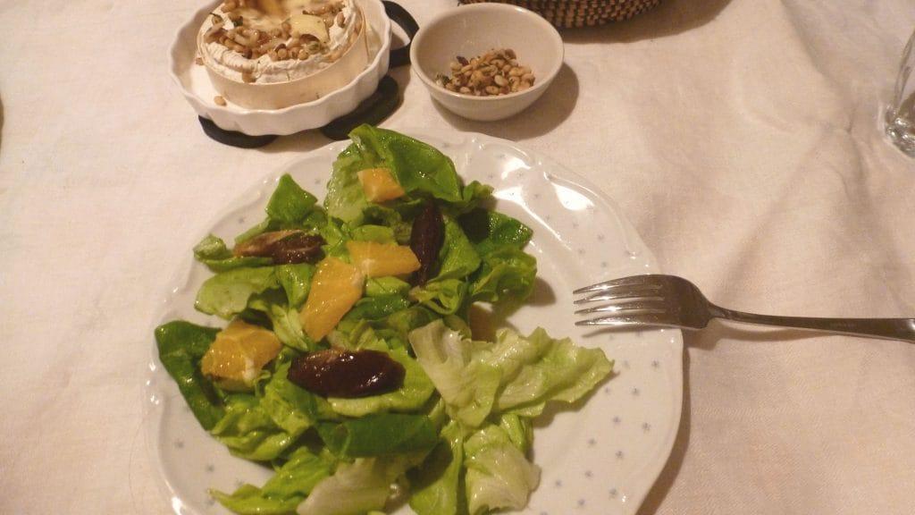 Wit bord met groene bladsla, sinaasappel en dadels