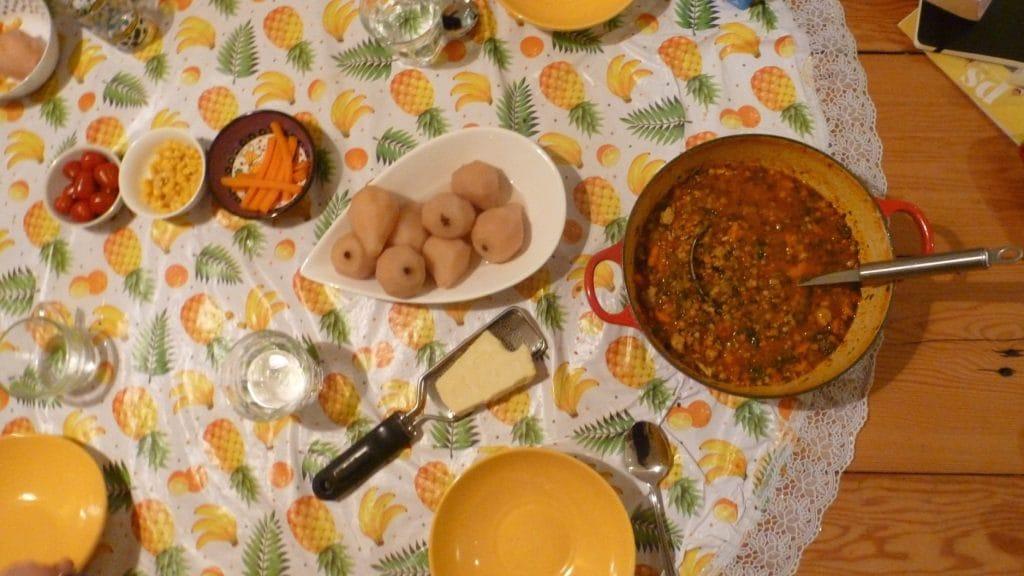 Pan linzensoep naast schaal stoofperen en rasp met stuk kaas