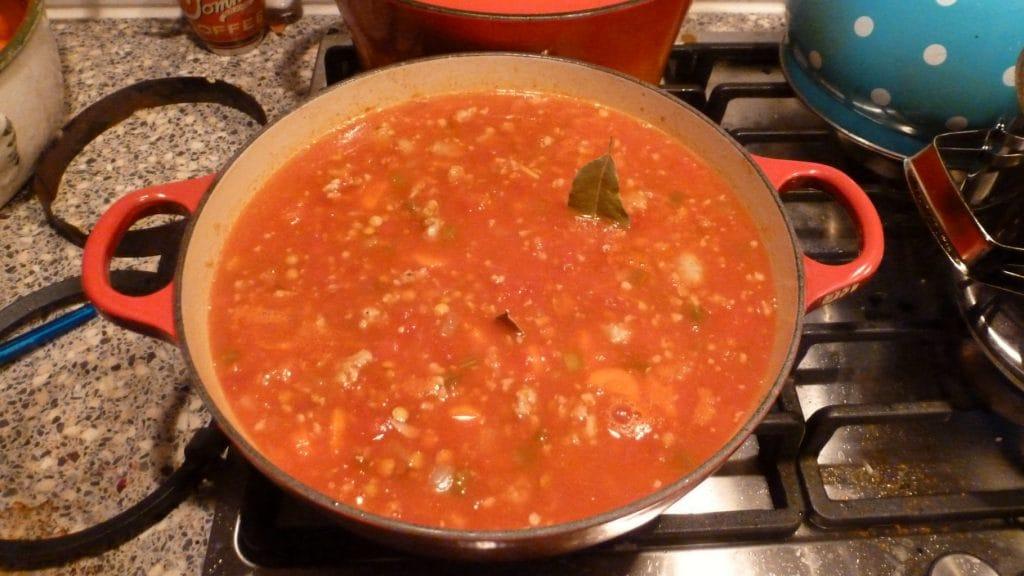 Volle pan met rode soep met laurierblaadjes