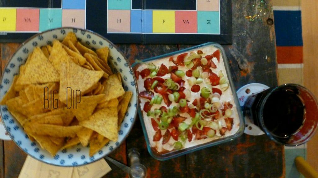 Romig witte dip met tomaatjes en lenteui naast schaal tortillachips