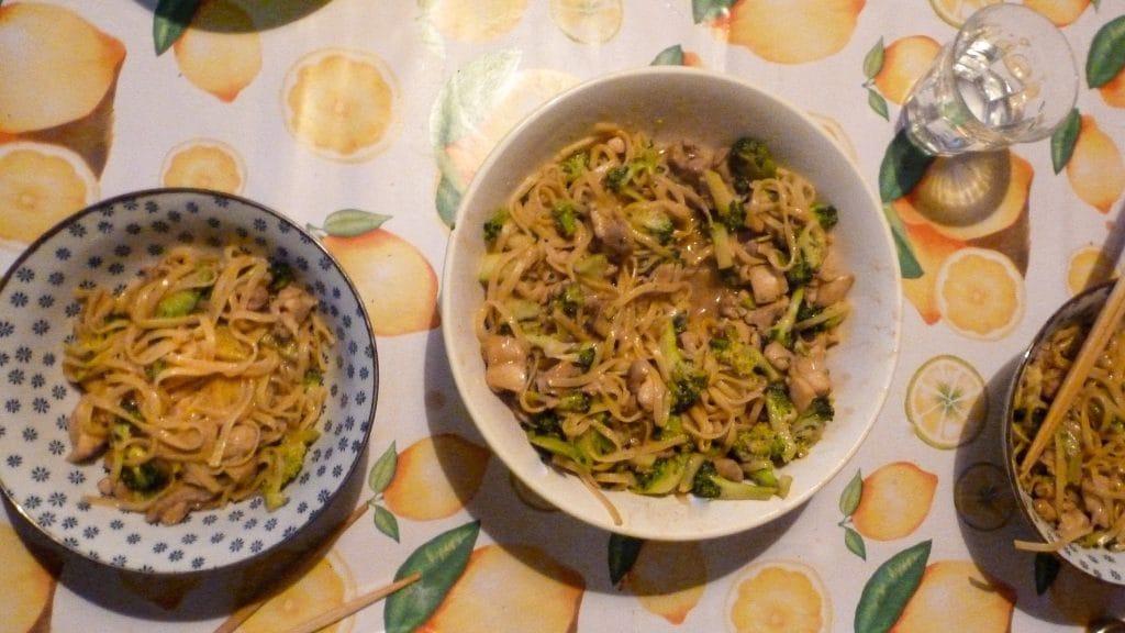 Schaal noedels met kip en broccoli op tafel