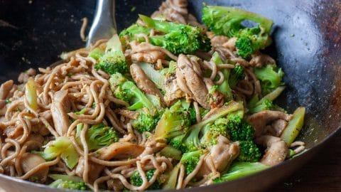 Zwarte wok met daarin lichtbruine reepjes kip en groene broccoli. Aan de linker bovenkant zie je nog net de metalen steel van een wokschep