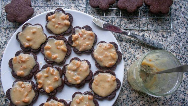 Chocoladekoekjes op een bord met een potje kokoskaramel en pindas ernaast