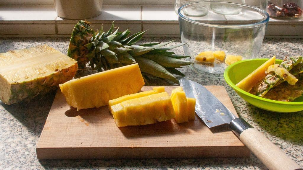 Gesneden ananas op een plank met een mes ernaast