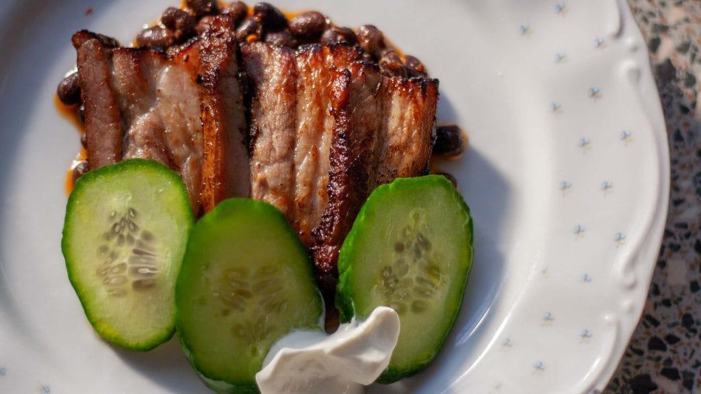 Geroosterd buikspek met bonen en komkommer