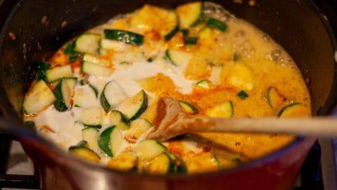 Donkergrijze pan met lichtoranje courgettesoep met schijfjes groene courgette. Erin ligt een houten pollepel.
