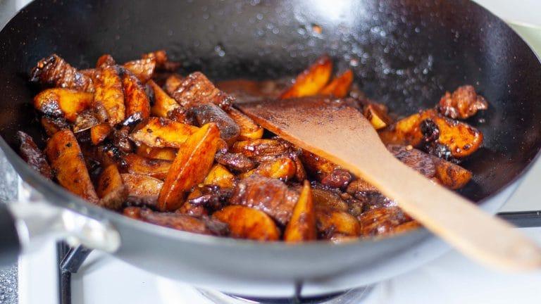 Zwarte wok met partjes aardappel en reepjes biekstuk in rood-bruine saus