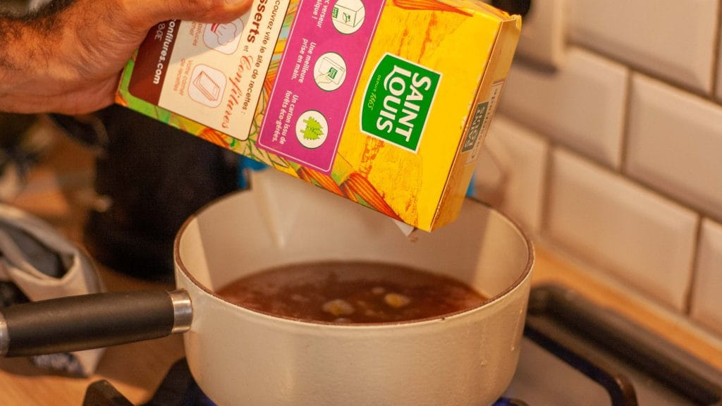 Pak suiker boven een pan chai thee