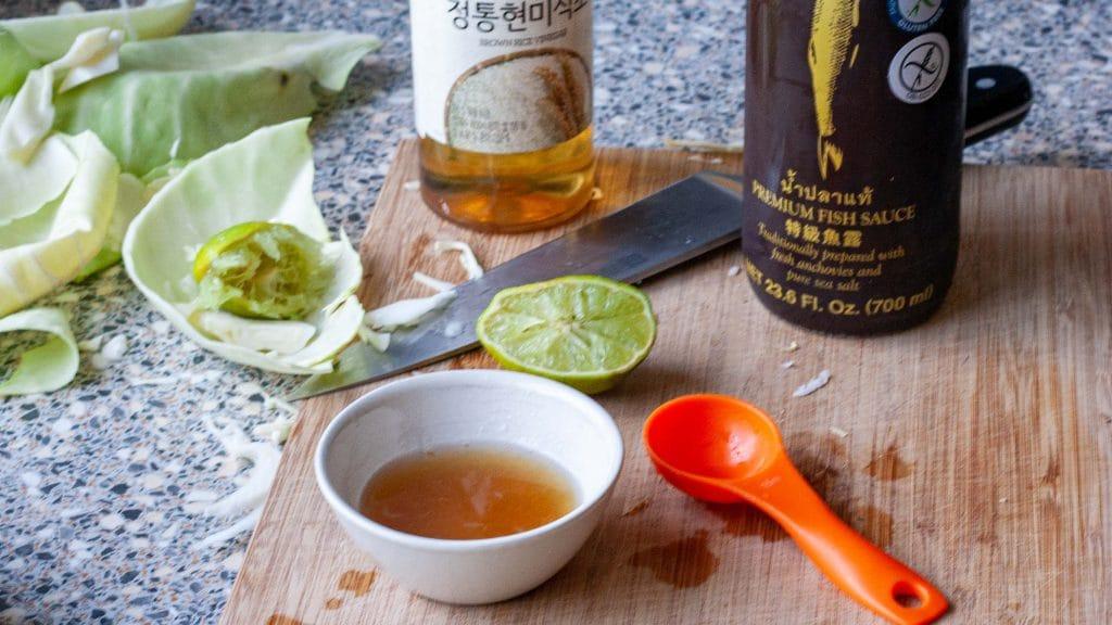 Schaaltje bruine dressing naast oranje maatlepel met op de achtergrond een halve limoen en twee flessen