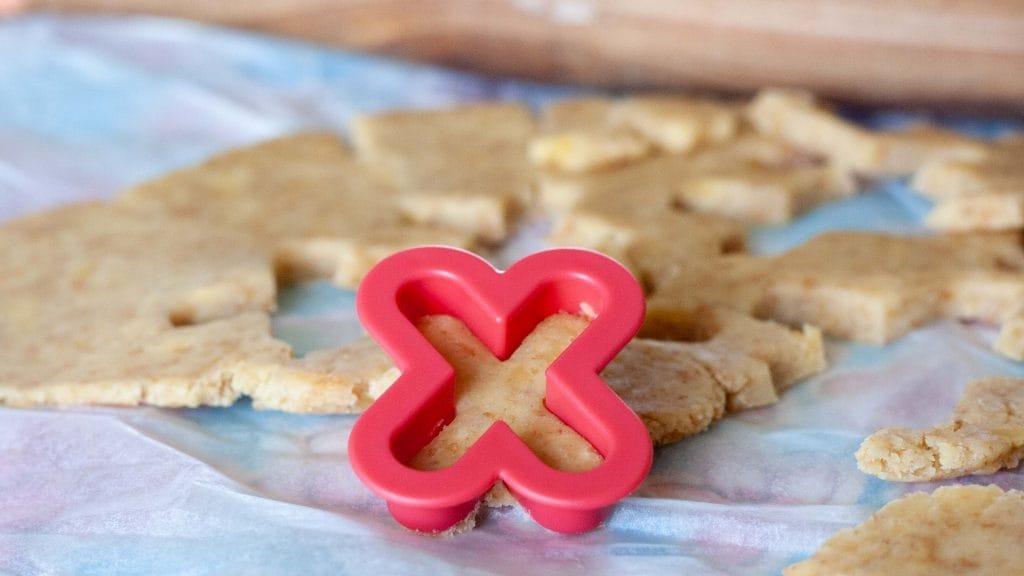 Roze koekjessteker in de vorm van een X met  kaaskoekjesdeeg erin