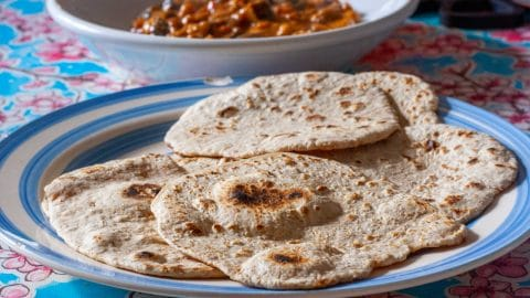 Stapel chapati op wit bord met blauwe cirkels met curry op de achtergrond