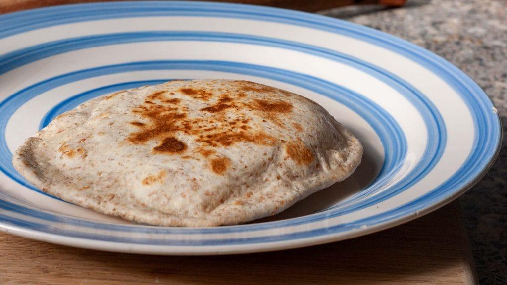 Plat brood met bruine plekjes op wit bord met blauwe cirkels
