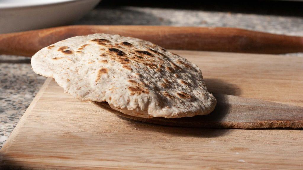 Rond broodje met bruine schroeiplekjes ligt op houten spaan op plank met op de achtergrond een deegroller