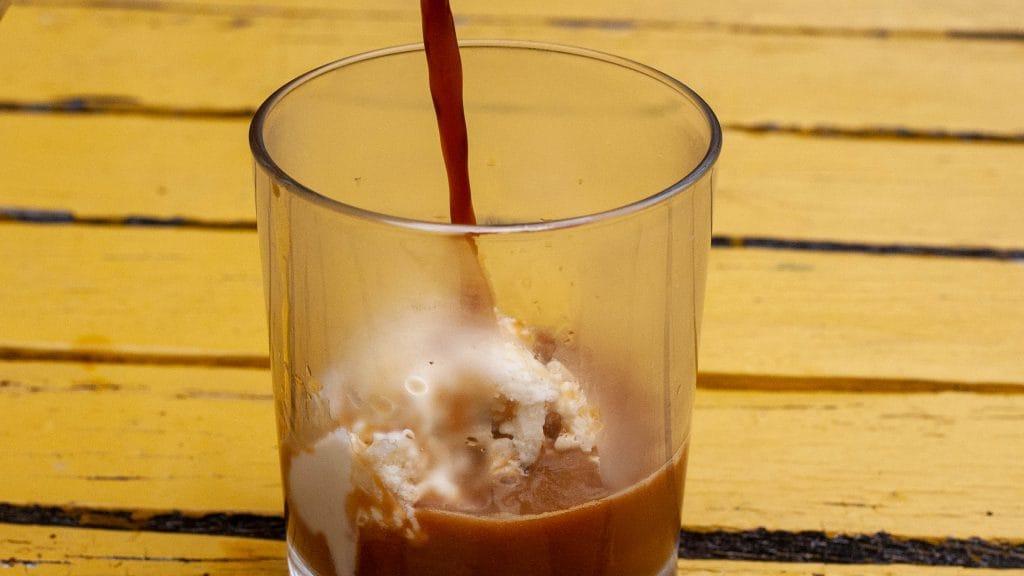 Glas met een wit bolletje ijs waar een bruine straal koffie overheen wordt geschonken