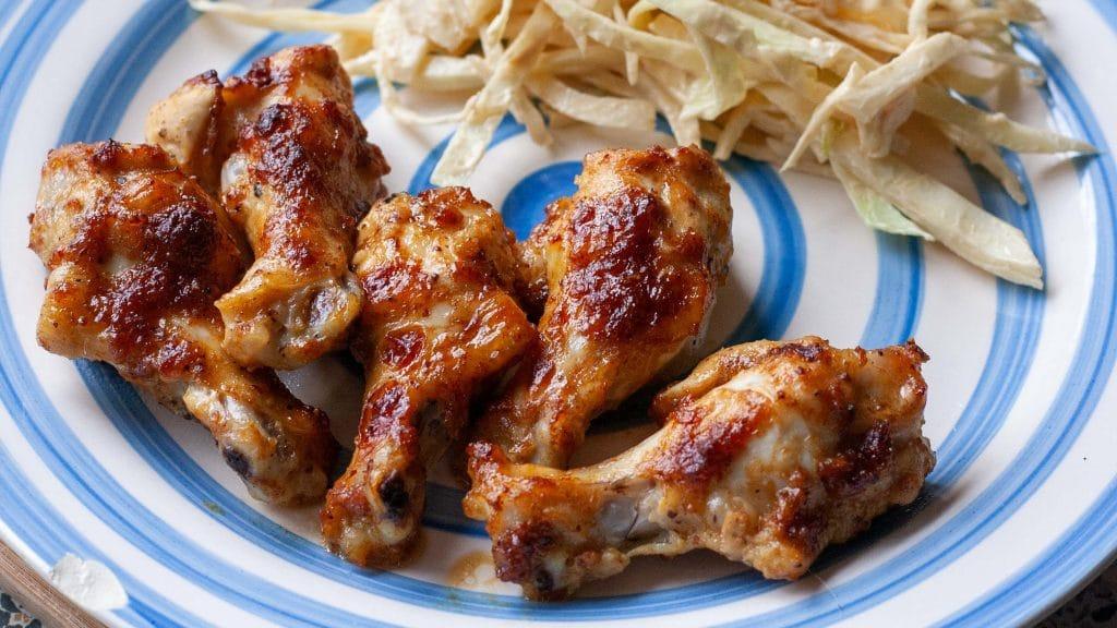 Wit met blauw bord met daarop goubruine kipvleugels en op de achtergrond witte koolsalade