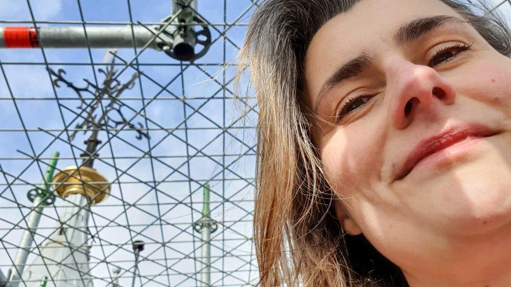 Lachende selfie met links daarnaast een windwijzer achter een hek