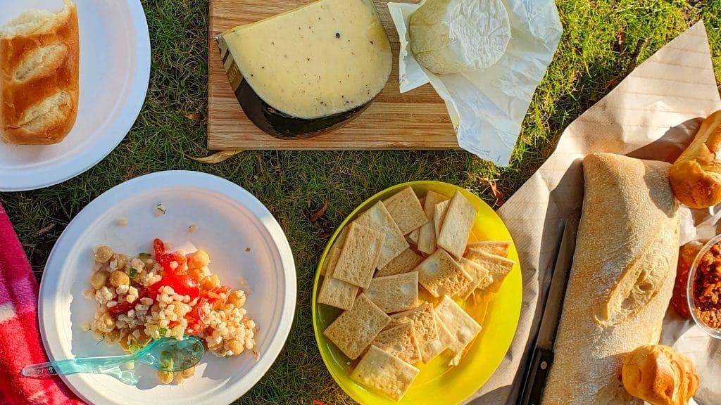 Wit bordje salade met tomaten, geel bordje crackertjes, plankje met kaas en brood op een stuk papier op het gras