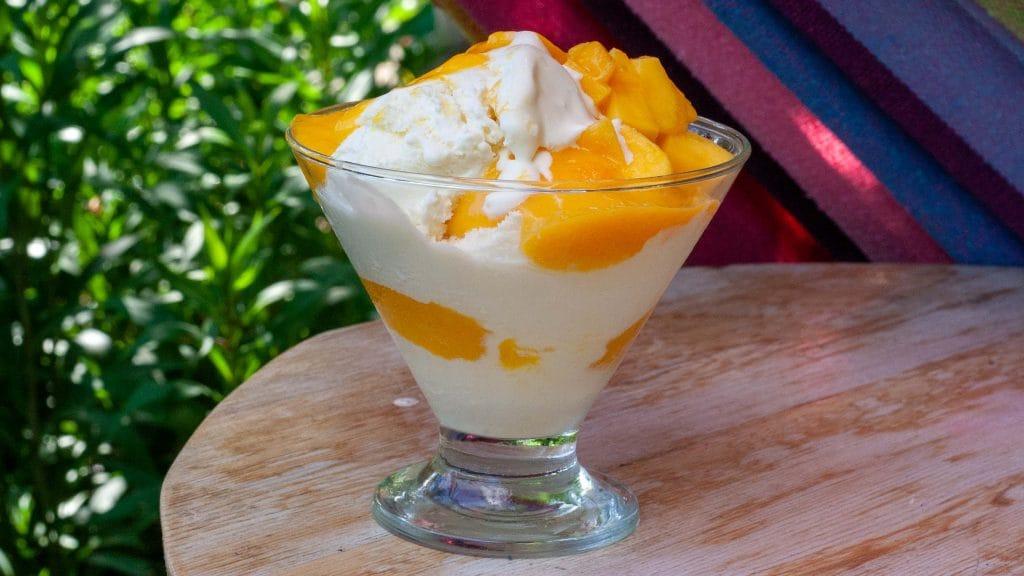Glas wit ijs met oranje saus en stukjes mango, op een houten tafel