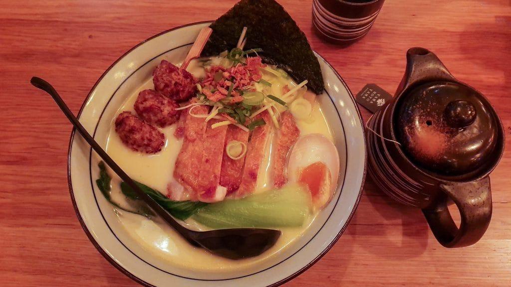 Kom witte soep met plakken lichtbruine kip en bruine kipballetjes aan een stokje