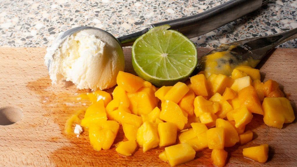 Houten plank met oranje stukjes mango, een bolletje wit ijs in een ijslepel en een halve limoen
