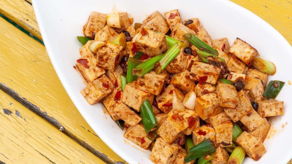 Geel geverfde latten met daarop een witte schaal met blokjes tofu in oranje-bruine Szechuan saus met stukjes groene bosui