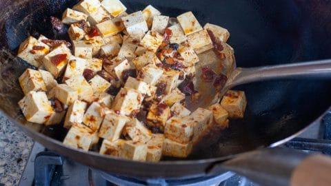 Zwarte wok met witte blokjes tofu met wat oranje Szechuan saus