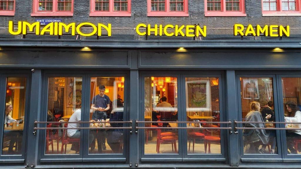 Ramen en deuren met zwarte kozijnen met daarboven de woorden Umaimon chicken ramen in grote gele letters