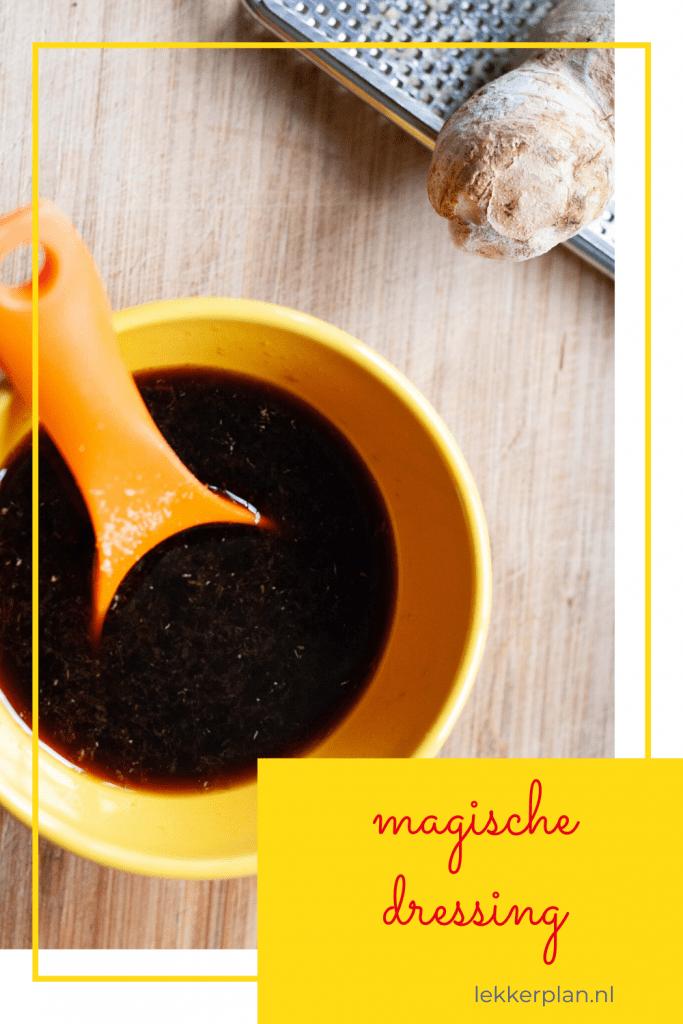 Geel bakje met zwarte dressing en een oranje lepel. De ondergrond is van hout en we zien een klein stukje van een rasp met een stuk gember.