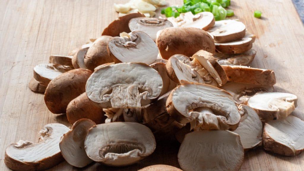 Plank met plakjes rauwe champignon