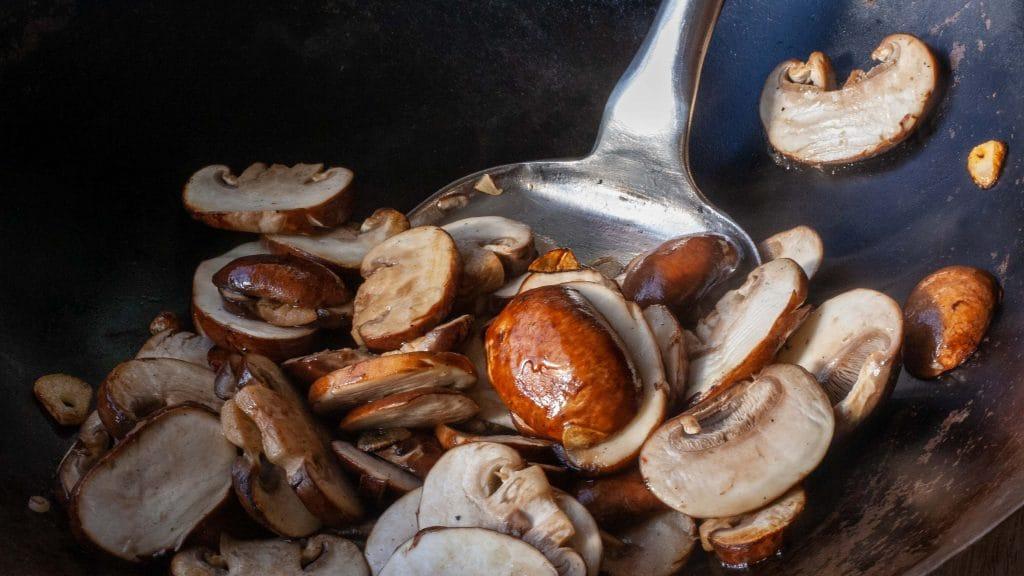 Champignons bakken in de wok, met een metalen spatel.