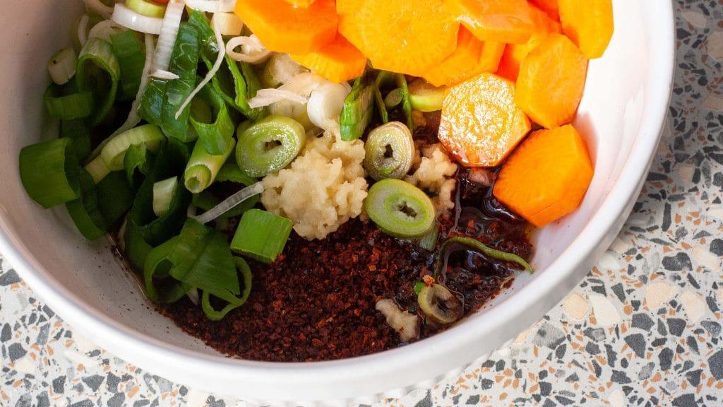 Wit bakje met plakjes wortel, ringetjes groene lente-ui, geperste knoflook, vissaus en chilipoeder