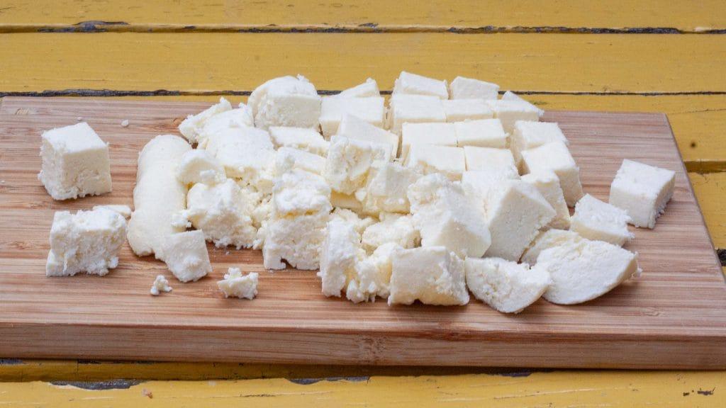 Gele plankjes met daarop een bamboe plank met blokjes kruimelige witte kaas